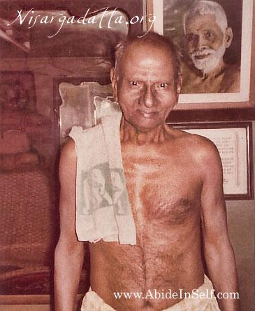 013-0-Nisargadatta Maharaj with a photo of Sri Ramana Maharshi behind.jpg