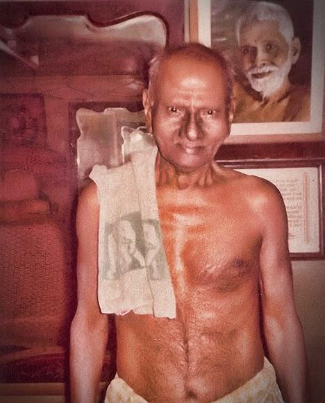 013-1Nisargadatta Maharaj with a photo of Sri Ramana Maharshi behind.jpg