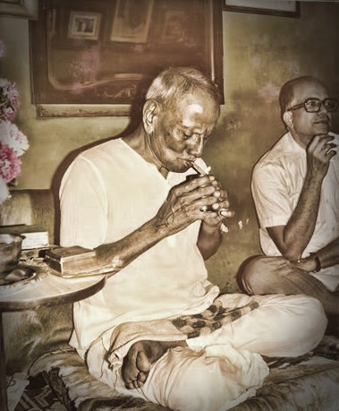 044-Nisargadatta Maharaj lighting up a beedi.jpg