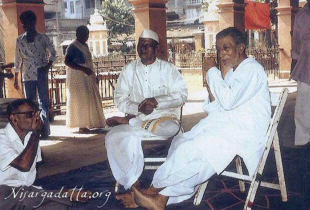 153-1-Nisargadatta Maharaj with Ranjith Maharaj, Mullarpattan sitting on the floor.jpg